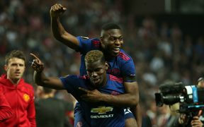 Manchester United's Paul Bogba (bottom) and Timothy Fosu-Mensah (top) celebrate their Europa win.