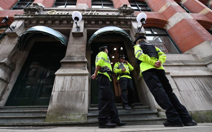 Police officers stand on duty following a raid at Granby House, close to Manchester Piccadilly railway station in Manchester.