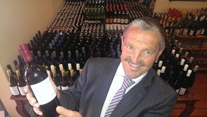 Bruce Richards with the extensive wine collection for sale.