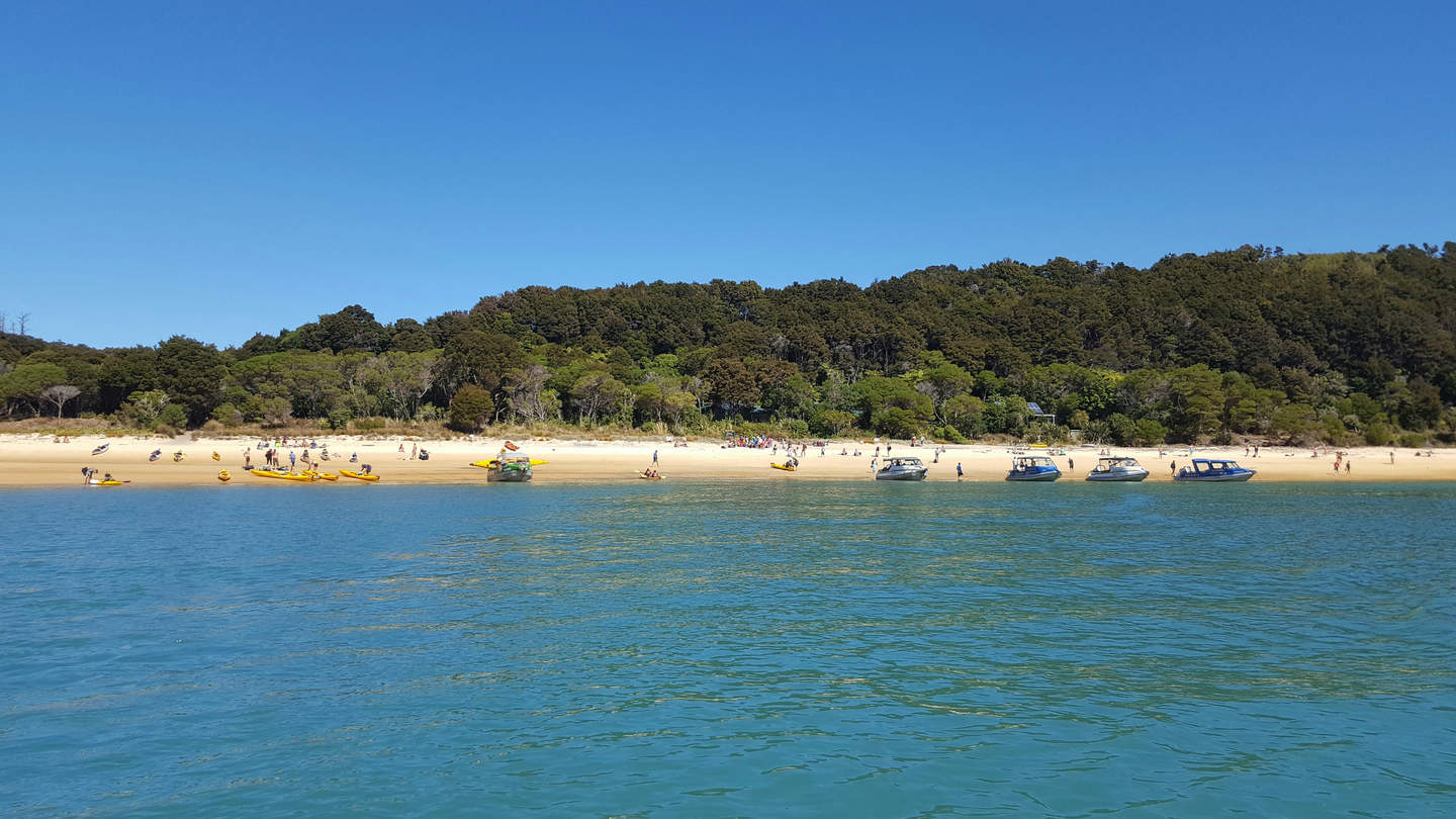 Boats and water taxis line the beach at Anchorage, Abel Tasman National Park in March 2017 - well after the peak tourist season