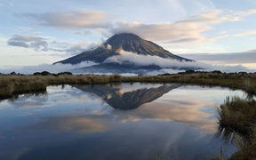 Mount Taranaki is reflected in a tarn on the Pouakai Crossing