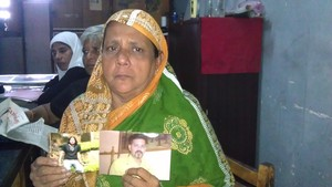 A Sri Lankan woman holds pictures of her missing son.