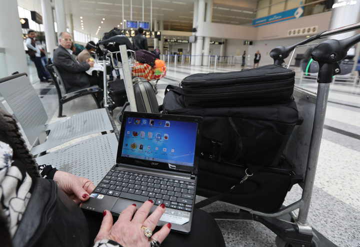 Woman at Beirut international airport checking laptop. March 2017.