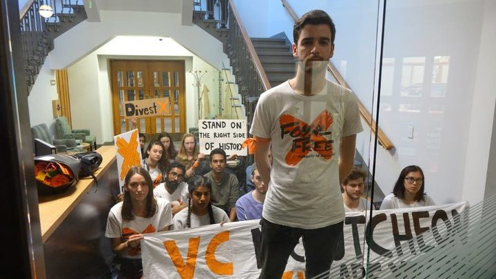 Alex Johnston, from Fossil Free University of Auckland, with other protesters locked in the Vice-Chancellor's reception area by campus security, after occupying a wing of the administration block.