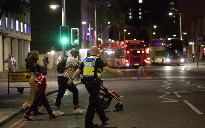 London police help escort people away from the scene of an apparent attack near London Bridge.