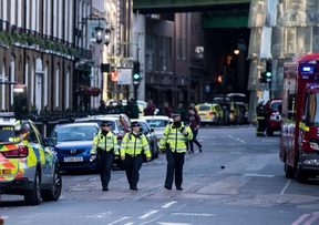 Police officers and emergency response vehicles are seen on the street outside Borough Market.