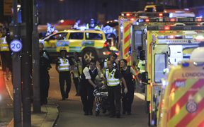 Police and members of the emergency services attend to a person injured in the London Bridge attack.