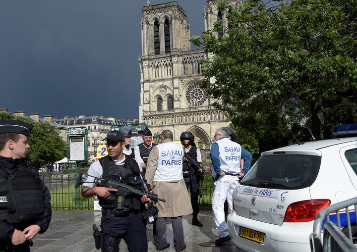 French police officials and investigators gather near the entrance of Notre Dame cathedral in Paris after police shot and injured a man who had tried to attack an officer with a hammer.