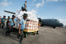 Philippine police help load an RNZAF C-130 Hercules with food for typhoon survivors.