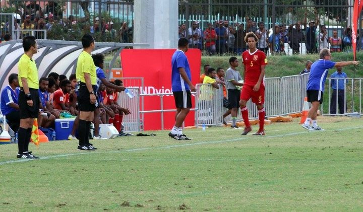 PNG defender Felix Komolong heads to the sideline after being shown a red card.