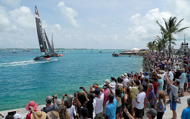 America's Cup defender sails by the crowds on shore at Bermuda.