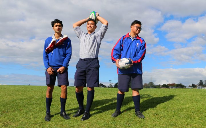 Three teenagers stand with rugby  balls on a field.