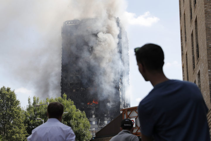 People look up towards Grenfell Tower as daylight revealed the 24-storey block still burning.