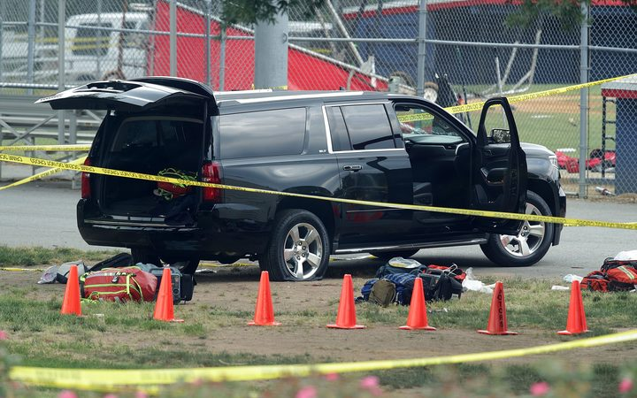 A black SUV with a shot-out windscreen at  the scene of the shooting.