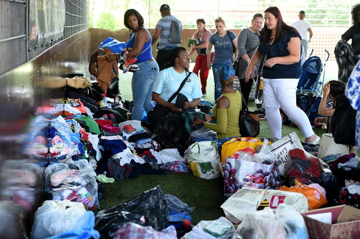 Local residents sort through clothing donated clothes for the evacuees from the burned tower block.