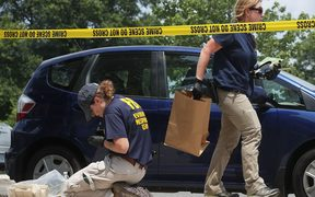 Members of the FBI Evidence Response Team collect evidence at the site of the shooting at Eugene Simpson Stadium Park.