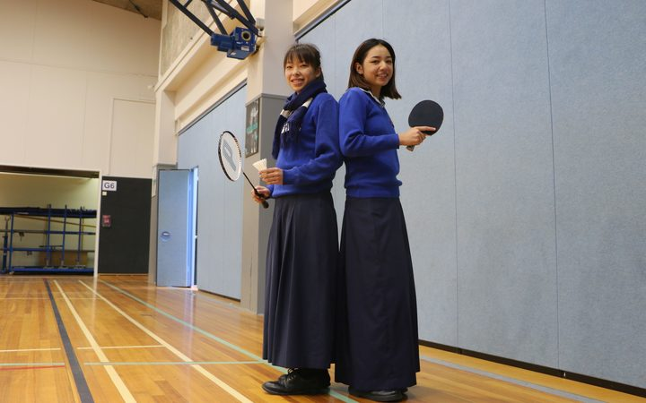 Two young women stand back to back insports hall with bat and racquet