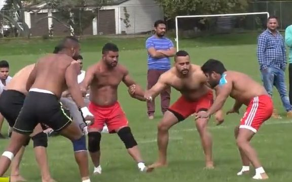 Men with shirts off and sports shorts watchfully in a circle as part of the Indian sport Kabbadi