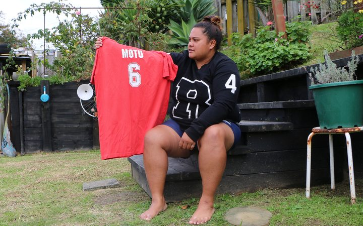Woman sits on step in her garden holding her red kabbadi shirt