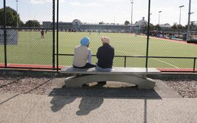 Two Sikh men sit beside a hockey pitch