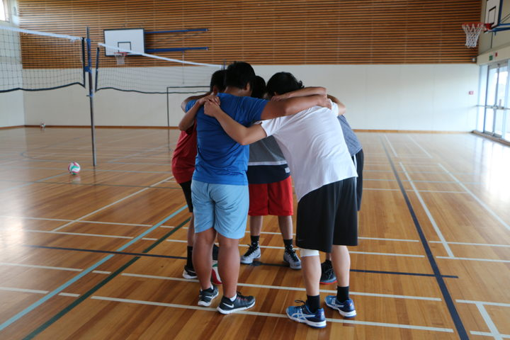 Four teenagers in sports huddle in gym