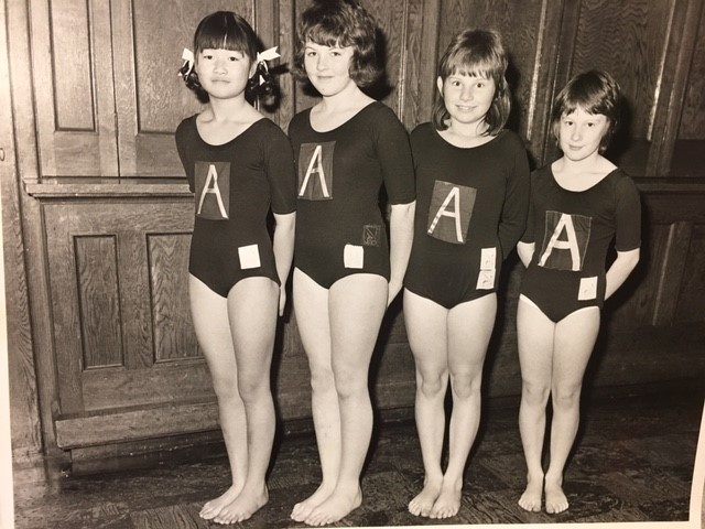 Four young gymnasts in a line