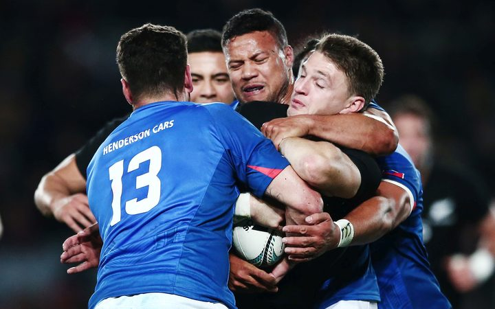 Beauden Barrett is wrapped up by Alapati Leiua and Kieron Fonotia during the Pasifika Challenge test between the All Blacks and Manu Samoa.