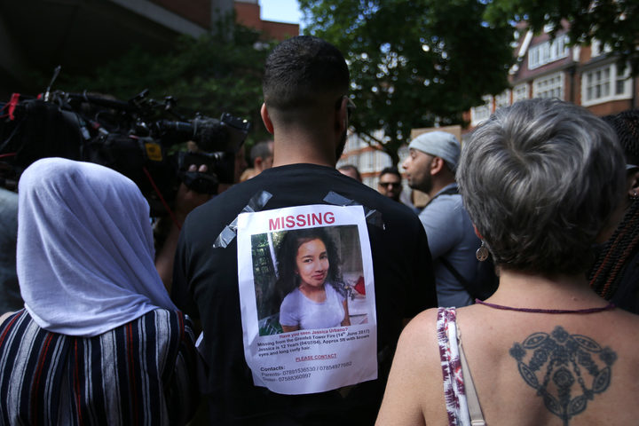 A man carries a picture of a missing person on his back, during a protest outside Kensington Town Hall, London.