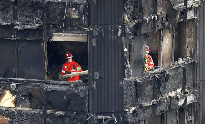Members of the emergency services work on the middle floors of the charred remains of the Grenfell Tower block.