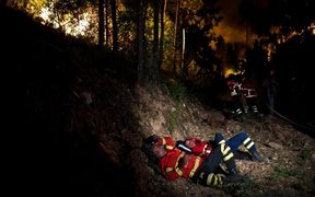 Firefighters rest during a wildfire at Penela, Coimbra, central Portugal.
