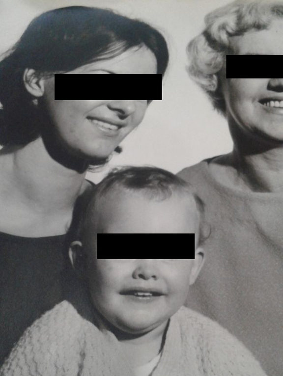 "A portrait of ""Carol"" with her mother and son. Their faces are blacked out."