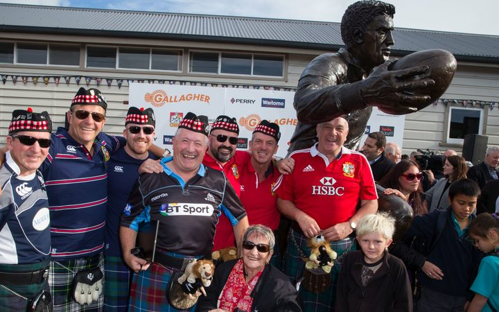 British and Irish Lions fans crowd the statue for a photo at the official unveiling of All Black legend Sir Colin Meads bronze statue, and opening of the Meads brothers exhibition in Te Kuiti.