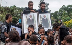 People in Port Vila mourn during the funeral procession of the late president Baldwin Lonsdale