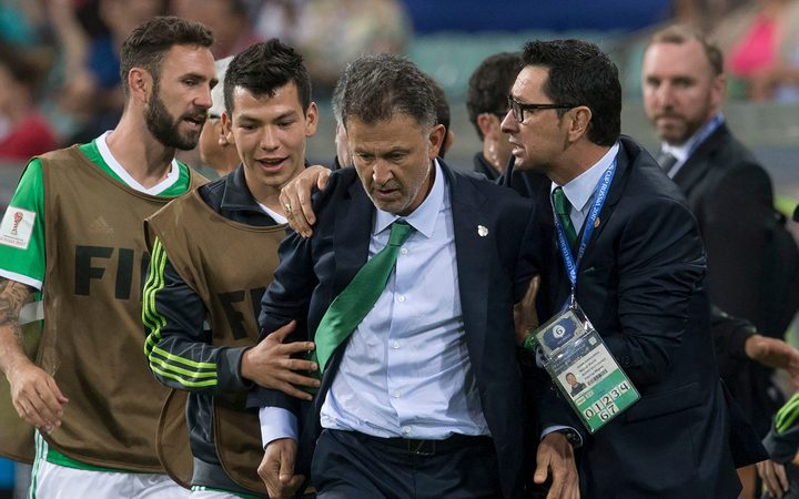 Juan Carlos Osorio (MEX) restrained by players and officials during the match Mexico vs New Zealand.