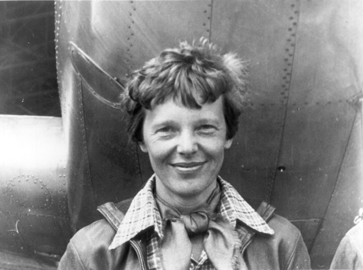 Amelia Earhart standing under the nose of her Lockheed Mode 10-E Electra
