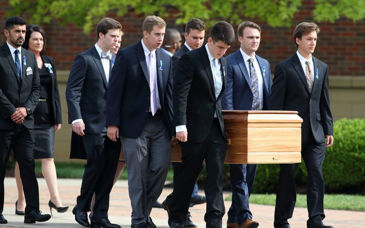 The casket carrying the remains of Otto Warmbier is carried out of Wyoming High School after his funeral.