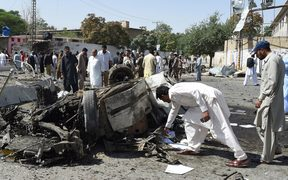 Pakistani security officials inspect the site of a powerful explosion that targeted a police vehicle in Quetta on June 23, 2017