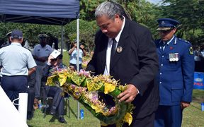 A family member lays a wreath at the RAMSI memorial
