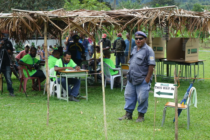 Police and electoral officials call out names of voters to come and vote, Timini, Morobe Province.