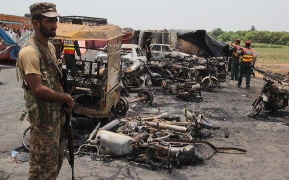 Pakistani soldiers stand guard beside burnt out vehicles at the scene where an oil tanker caught fire following an accident on a highway near the town of Ahmedpur East.