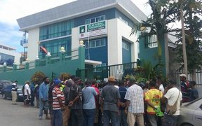 A crowd gathers outside the headquarters of PNG's electoral commission as news spreads of the arrest of senior officials.
