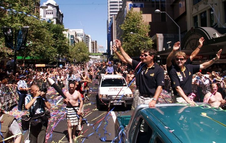 Russell Coutts (2/R) waves to the hundreds of thousands of specatators who turned up for a ticker-tape parade before the America's Cup is presented to Team New Zealand in Auckland, 04 March 2000