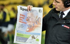 A television host holds up a newspaper with an image of British and Irish Lions coach Warren Gatland depicted as a clown before their rugby union match against the Wellington Hurricanes at Westpac Stadium in Wellington on June 27, 2017.