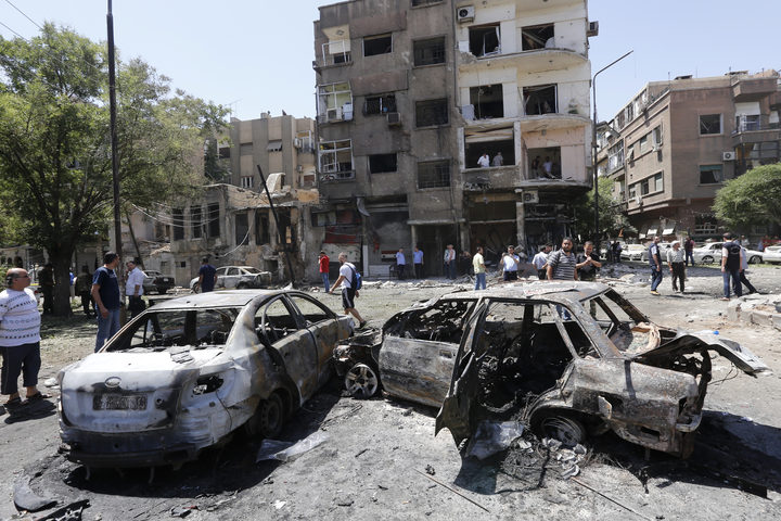 Charred vehicles at the site of a suicide bomb attack in the Syrian capital Damascus