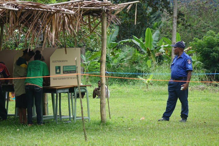 A police officer watches over polling in Papua New Guinea's election.