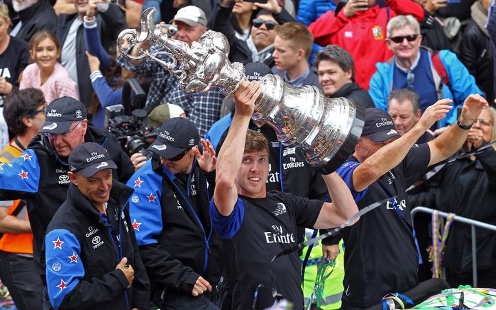 Team NZ helmsman Peter Burling holds the America's Cup high at the Auckland parade.