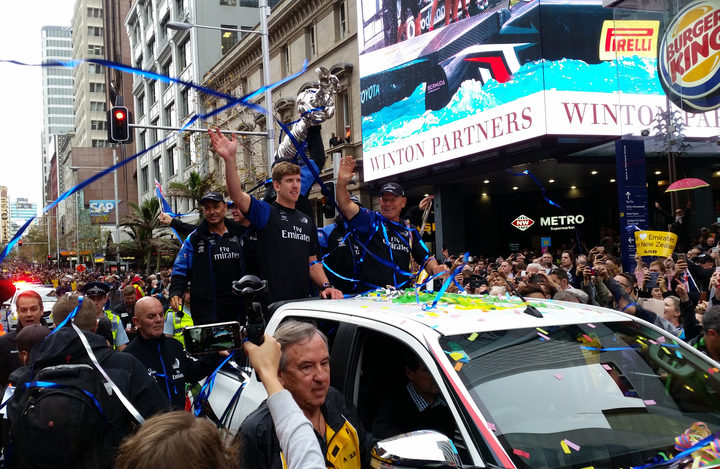 Peter Burling and Team NZ wave to crowds on Queen Street