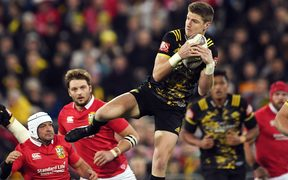 Jordie Barrett of the Hurricanes leaps for a high ball against the Lions.