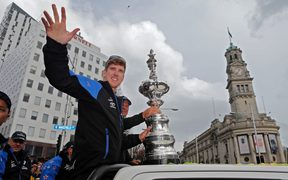 Peter Burling waves to the crowd at the America's Cup parade in central Auckland.