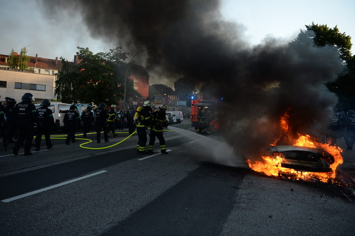 "THe fIRe brigade put out a car set alight during the ""Welcome to Hell"" rally against the G20 summit in Hamburg, northern Germany."